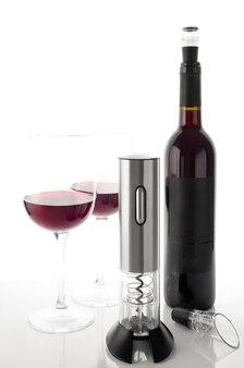 Cavatappi elettronico a batteria metallico. su uno sfondo bianco a specchio. vicino all'aeratore. sullo sfondo due bicchieri e una bottiglia di vino.