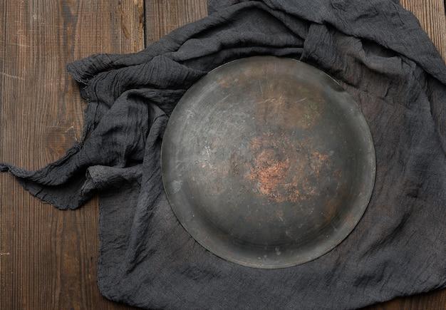 Piatto tondo metallico e strofinaccio da cucina nero