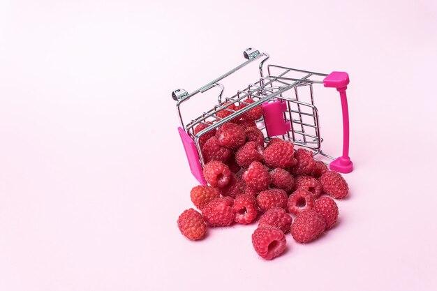 Carrello metallico piccolo con lamponi all'interno su sfondo rosa. shopping, acquisti