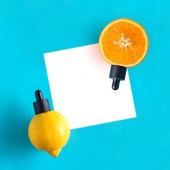 Metafora, bottiglia con siero, olio di agrumi, arancia, limone. il concetto di vitamina c nei cosmetici e nell'aromaterapia.
