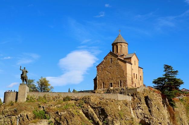 Chiesa di metekhi con la statua del re vakhtang gorgasali sullo sperone roccioso nella città di tbilisi, georgia