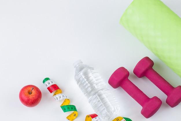 Metro, mela, acqua in bottiglia, manubri e tappetino yoga
