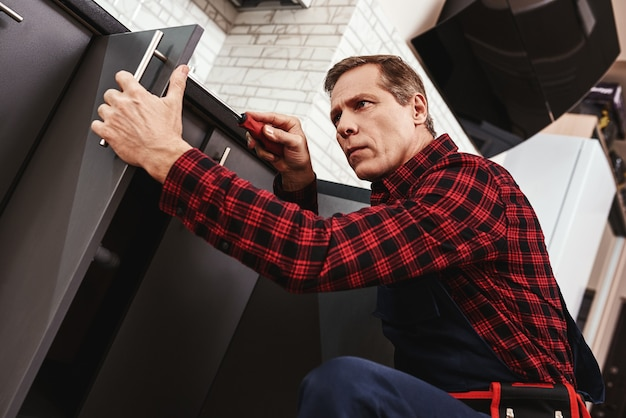 Primo piano del lavoro meticoloso del tuttofare anziano che ripara l'armadio da cucina