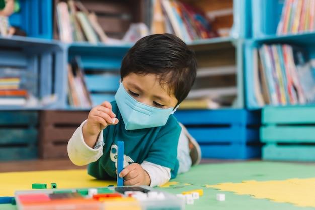 Bambino messicano a scuola con maschera facciale che gioca con pezzi colorati su un tappetino