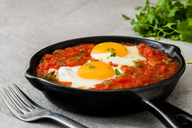 Rancheros messicani di huevos della prima colazione in padella del ferro su pietra grigia