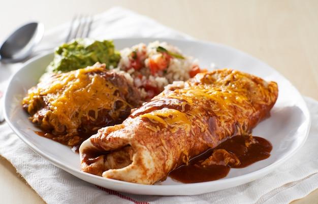 Piatto di burrito messicano con salsa enchilada rossa, fagioli fritti, riso e guacamole