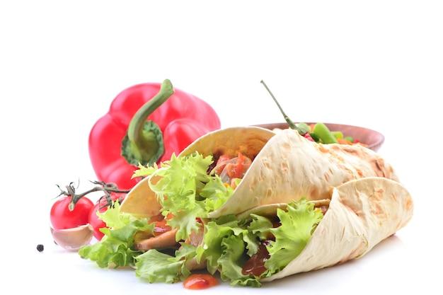 Burrito messicano con pollo e verdure su una superficie bianca