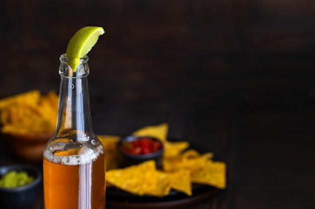 Cerveza messicana o orso con succo di lime e nachos snack messicani con guacamole.