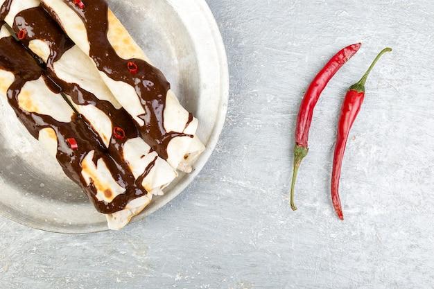 Enchiladas di pollo messicano con salsa di peperoncino e salsa al cioccolato poblano. cucina tradizionale latinoamericana. vista dall'alto. copia spazio.