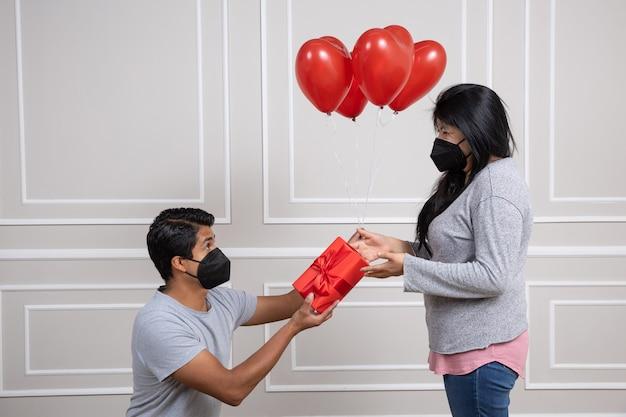 Coppia messicana. uomo che consegna il regalo di san valentino, indossa una maschera per il viso, nuova normalità