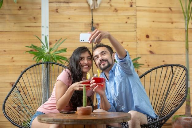 Coppia messicana che si fa selfie mentre lavora durante le vacanze estive summer