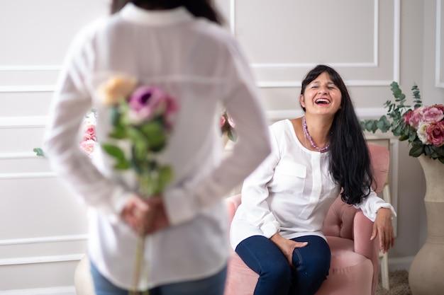 Figlia messicana che consegna fiori a sua madre il giorno della festa della mamma