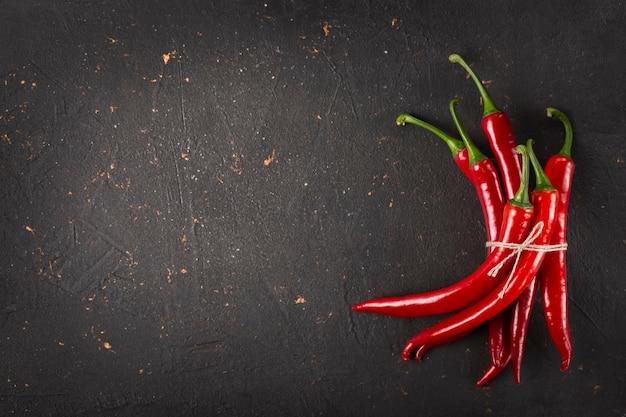 Messicano, essiccato, fiocchi di peperoncino, peperoncino verde, peperoni verdi, piatto laici, tavola nera, piccante, cinese Foto Premium