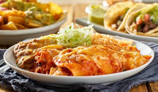 Piatto di enchilada messicana con salsa rossa, fagioli fritti e riso