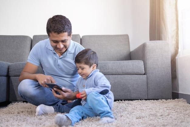 Padre e figlio messicani che esaminano telefono sul tappeto a casa