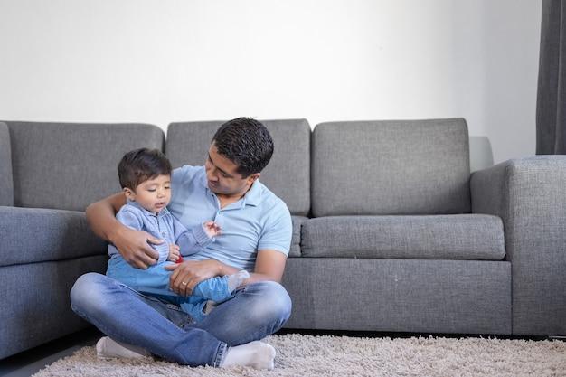 Padre e figlio messicani che giocano sul tappeto a casa