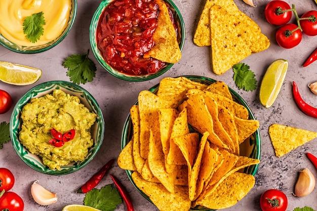 Sfondo di cibo messicano: guacamole, salsa, salse di formaggio con nachos, vista dall'alto.