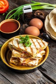 Quesadilla di piatto tradizionale di cucina messicana con uova strapazzate, verdure, prosciutto e formaggio