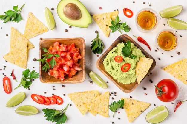 Selezione di feste di cibo messicano: salsa guacamole, salsa, patatine e colpi di tequila con lime.