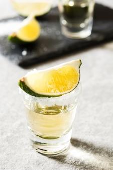 Tequila messicana d'oro con lime e sale su sfondo grigio