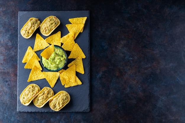 Salsa guacamole messicana con chips di nachos su una tavola di ardesia. tortilla chips e guacamole su uno sfondo scuro. copia spazio. vista dall'alto
