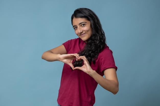 Donna latina messicana che fa il segno del cuore con le sue mani