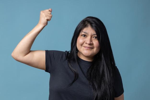 Donna latina messicana che mostra il potere della ragazza del bicipite