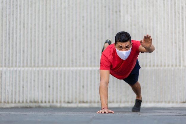 Uomo messicano che fa push up all'aperto che indossa una maschera facciale bianca