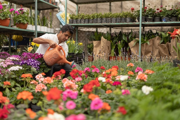 Uomo messicano che lavora in vivaio innaffiare le piante