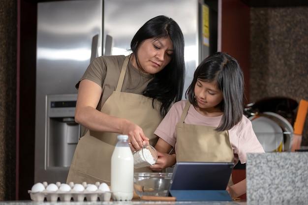 Madre messicana e figlia che cucinano in cucina guardando la ricetta su una tavoletta