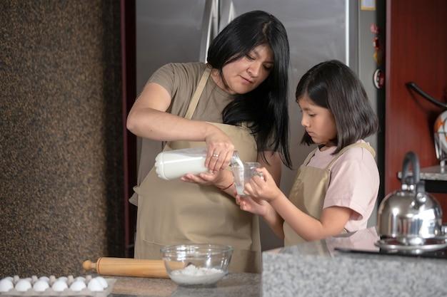 Madre messicana e figlia che cucinano in cucina, festa della mamma