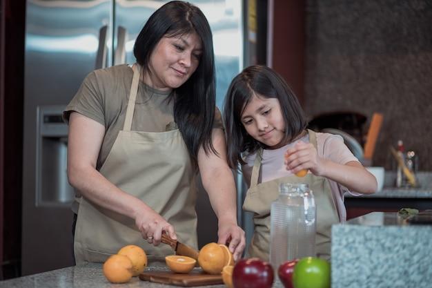 Madre messicana e figlia che preparano il succo d'arancia in cucina