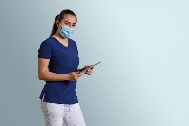 Infermiera messicana che lavora con il suo tablet digitale indossando maschera e maschera