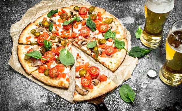 Pizza messicana con birra fredda. su fondo rustico.