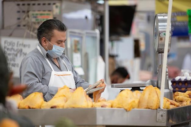 Negozio di pollame messicano, uomo che indossa la maschera per il viso, taglio di pollo crudo sul mercato pupular in messico