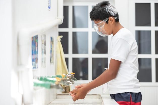 Studente messicano che si lava le mani a scuola per prevenire il coronavirus al ritorno a scuola