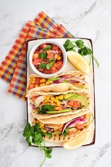 Tacos messicani con pollo alla griglia, avocado, chicchi di mais, pomodoro, cipolla, coriandolo e salsa al tavolo di pietra bianca. cibo di strada tradizionale messicano e latino americano. vista dall'alto.