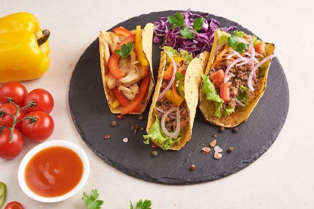 Tacos messicani con carne, tacos di strada carnitas di maiale in tortilla di mais giallo con cipolla, coriandolo e cavolo. cavolo rosso. vista dall'alto. laici piatta.