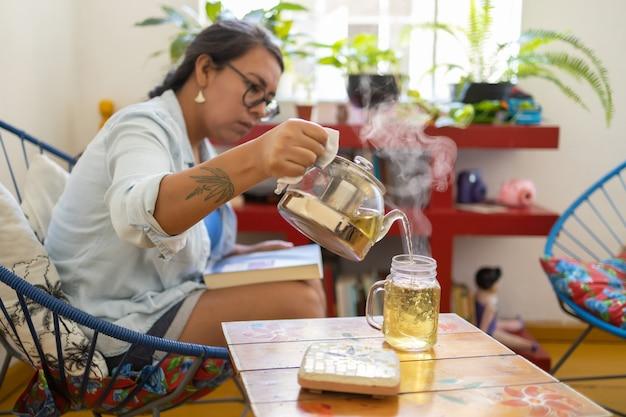 Donna millenaria messicana tatuata che serve tè caldo mentre legge un libro