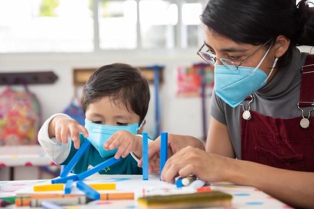 Insegnante messicana e bambino con mascherine a scuola dopo la quarantena covid-19