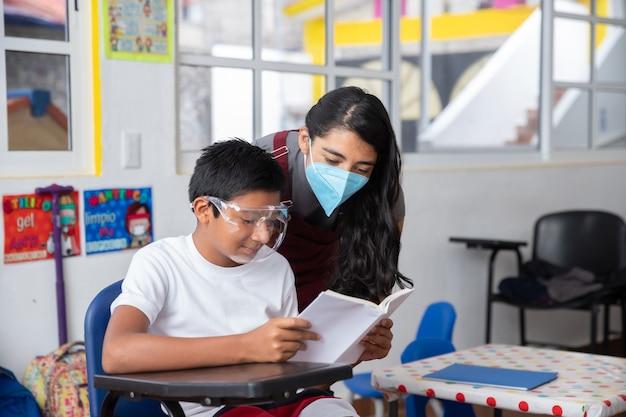 Insegnante e studente messicani che indossano la maschera facciale al ritorno a scuola dopo la pandemia di coronavirus