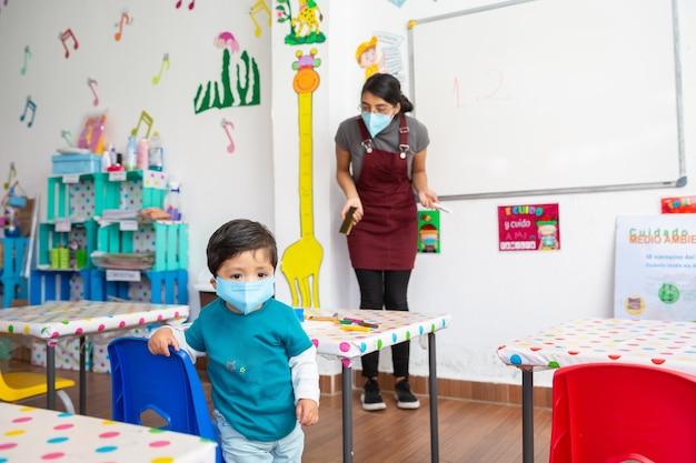 Insegnante messicana con maschera facciale che rimprovera bambino messicano con maschera facciale all'interno dell'aula Foto Premium