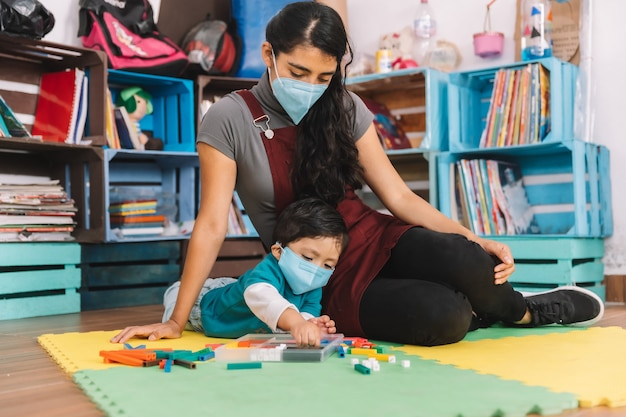 Insegnante messicana con maschera facciale che si prende cura e gioca con il bambino con maschera facciale all'interno della scuola