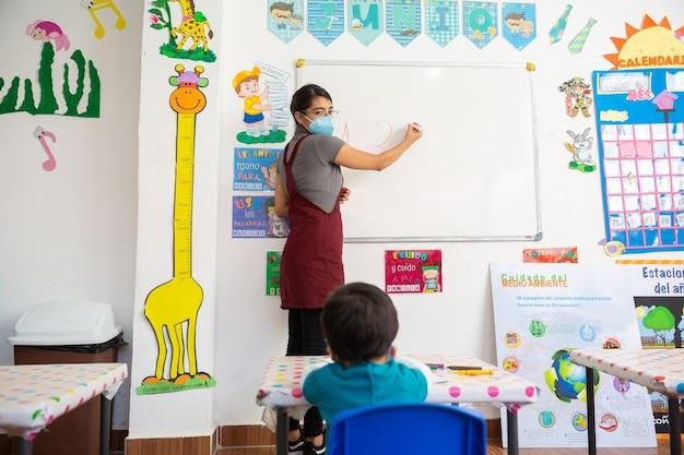Insegnante messicana con maschera facciale che scrive su lavagna bianca mentre insegna a un bambino messicano a scuola