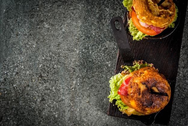 Tortilla de patate messicana rellena de jamón serrano in casseruola con patate, uova, sandwich con carne, lattuga, formaggio, pomodori. in padelle porzionate, con birra, tavolo nero. sopra