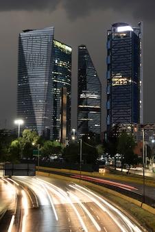Edifici di città del messico in una giornata piovosa e un viale in fondo con una serie di luci di automobili