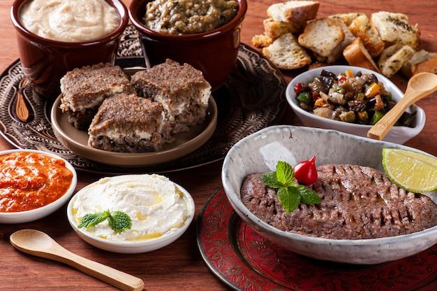 Meze è un set orientale di antipasti serviti in piccole ciotole con babaganoush, ricotta, hummus, muhammara e kibbeh