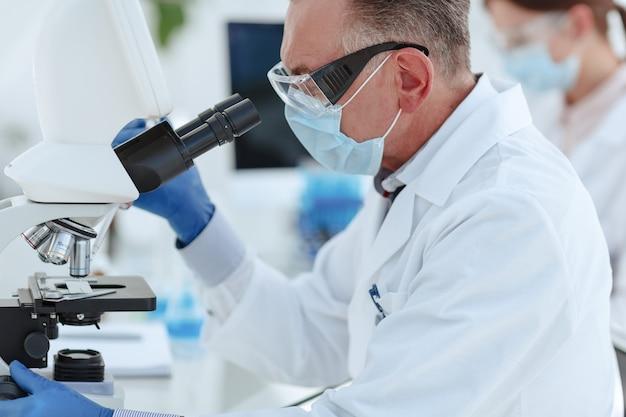 Microbiologo uno scienziato che guarda attraverso un microscopio