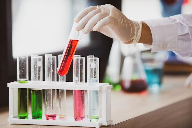 Microbiologo con provette di campione biologico contaminate da coronavirus