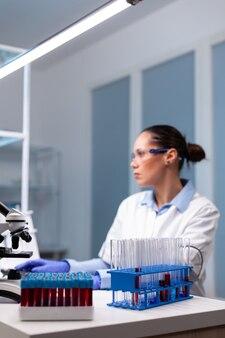Scienziato di microbiologia che digita esperimento di scoperta biochimica al computer